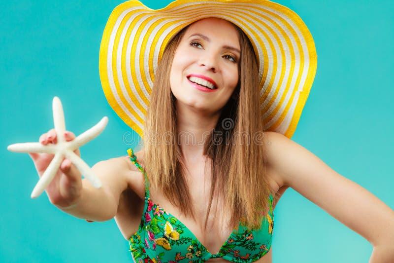 Mujer en el sombrero amarillo que lleva a cabo la c?scara blanca imagen de archivo