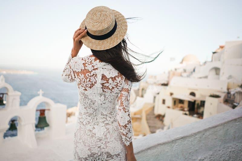 Mujer en el sombrero blanco del vestido y de paja en la isla de Santorini imagen de archivo libre de regalías