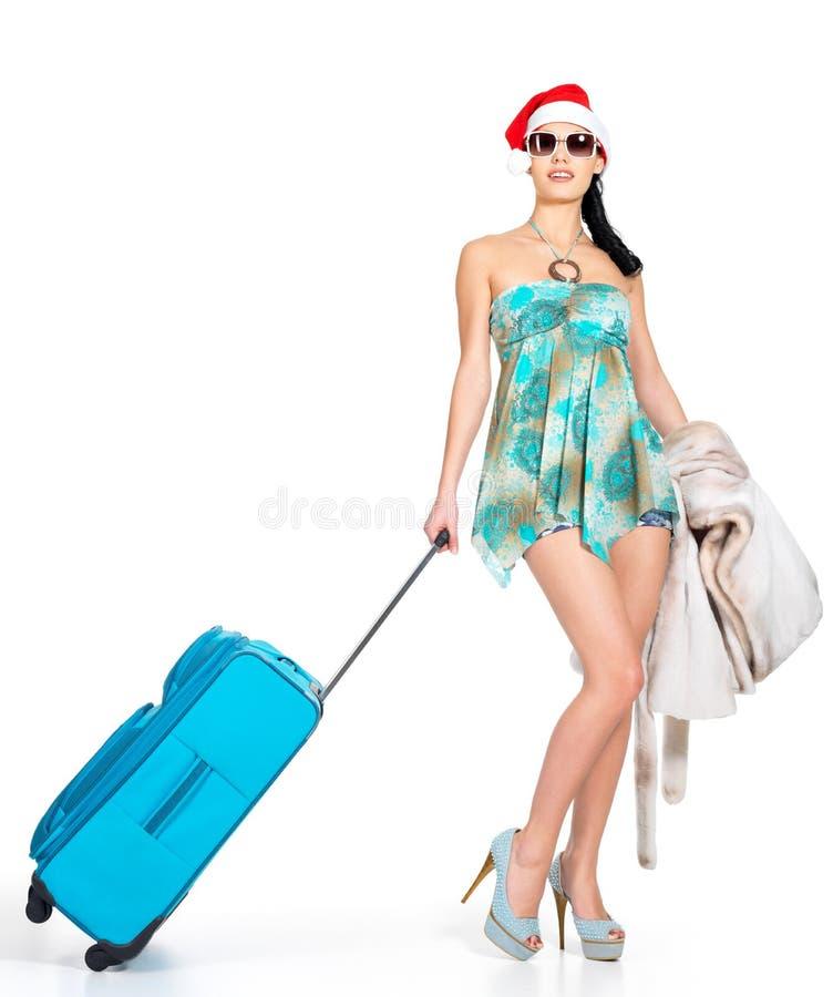 Mujer en el sombrero de santa que se coloca con la maleta del viaje imagen de archivo