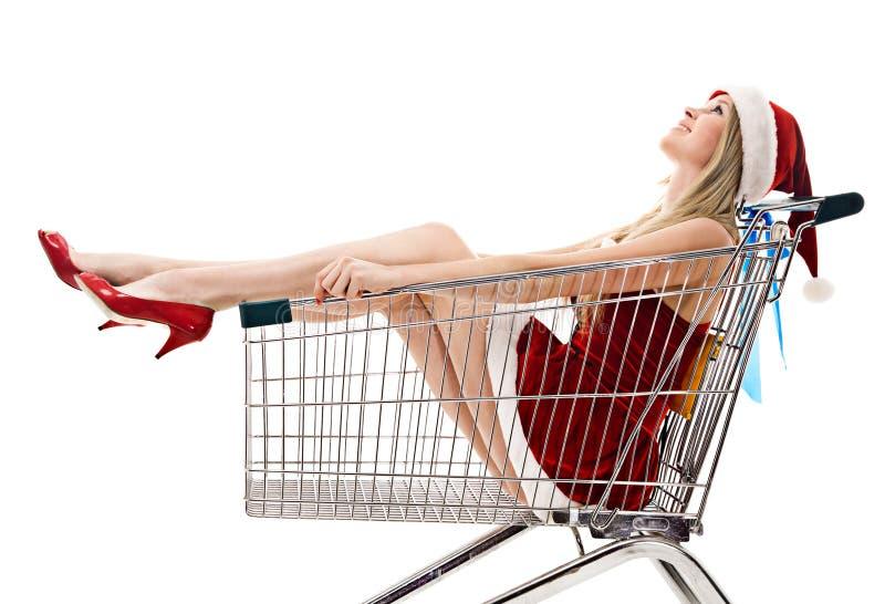 Mujer en el sombrero de santa que se sienta en carro de compras fotos de archivo libres de regalías