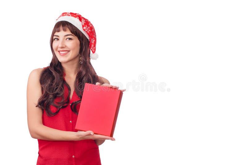 Mujer en el sombrero de santa que sostiene la caja de regalo de la Navidad aislada en blanco con el copyspace Muchacha salida fel imagen de archivo