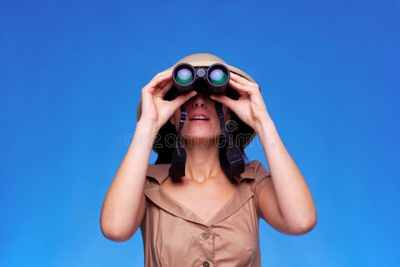 Mujer en el sombrero del safari que mira a través de los prismáticos imagen de archivo
