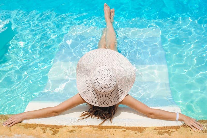 Mujer en el sombrero grande del whire que se relaja en la piscina foto de archivo