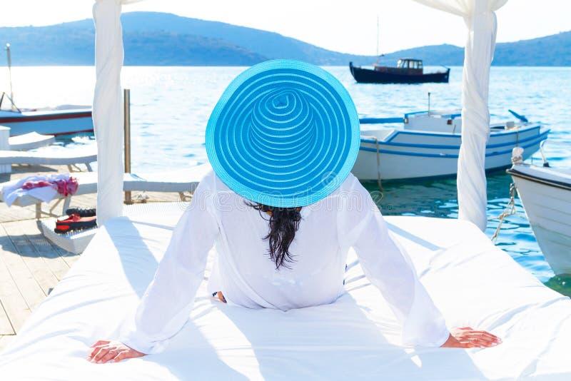 Mujer en el sombrero que se relaja en cama blanca de lujo imagenes de archivo
