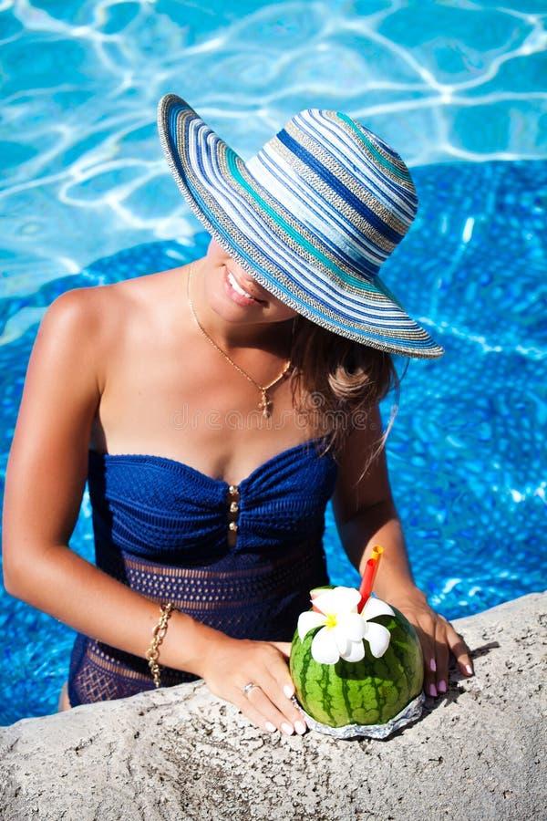 Mujer en el sombrero que se relaja en el poolside con el cóctel exótico fotografía de archivo