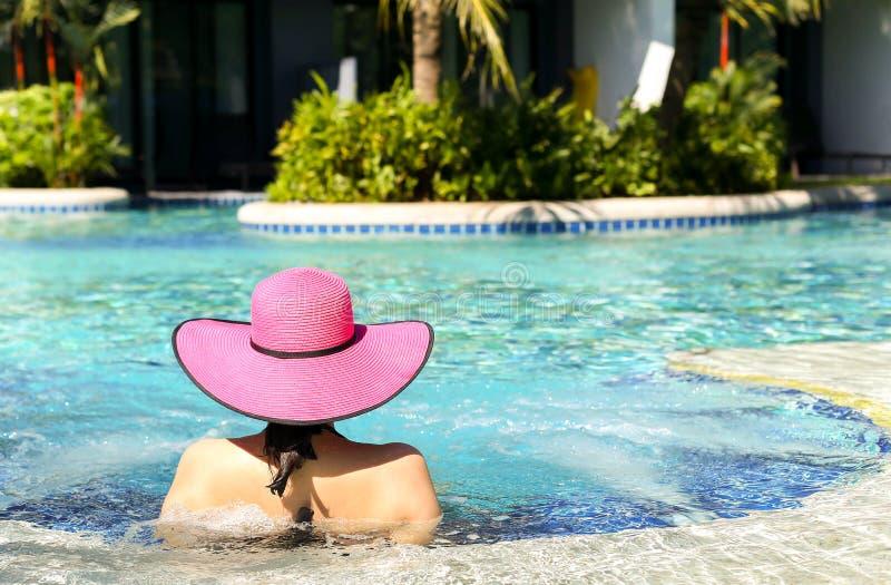 Mujer en el sombrero rosado que se relaja en piscina fotografía de archivo libre de regalías