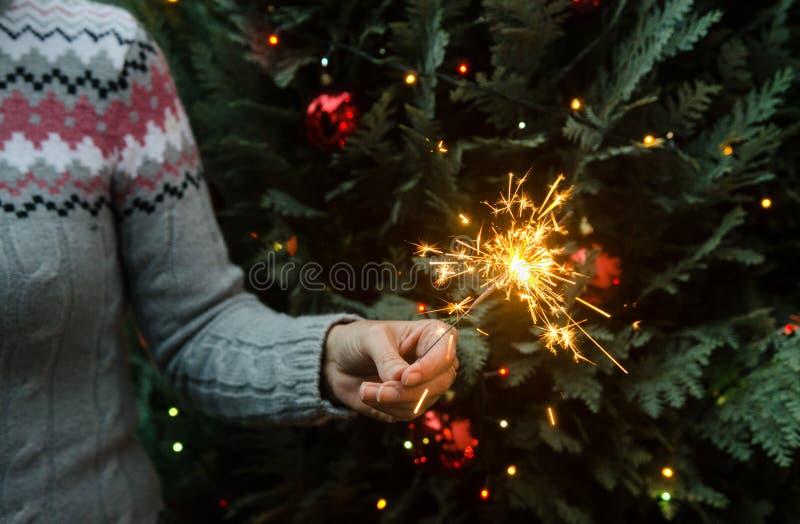 Mujer en el suéter hecho punto que sostiene bengalas antes de árbol de navidad imagenes de archivo