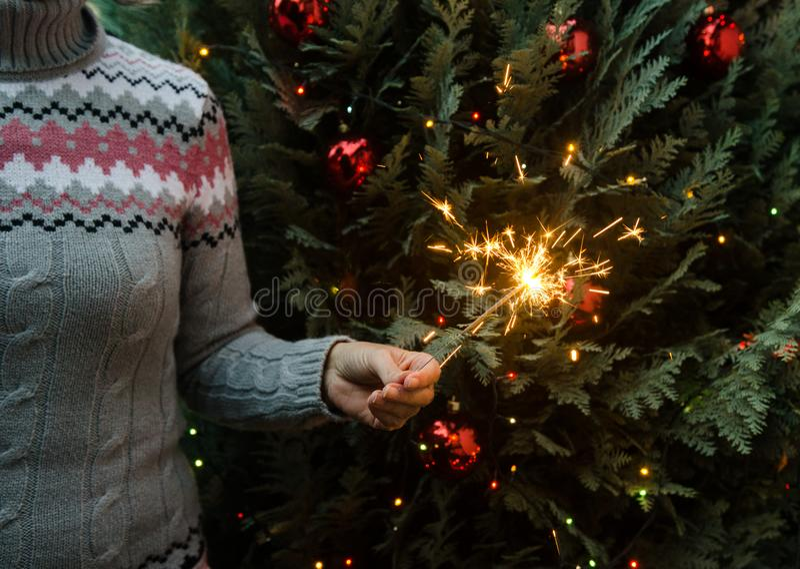 Mujer en el suéter hecho punto que sostiene bengalas antes de árbol de navidad imagen de archivo libre de regalías