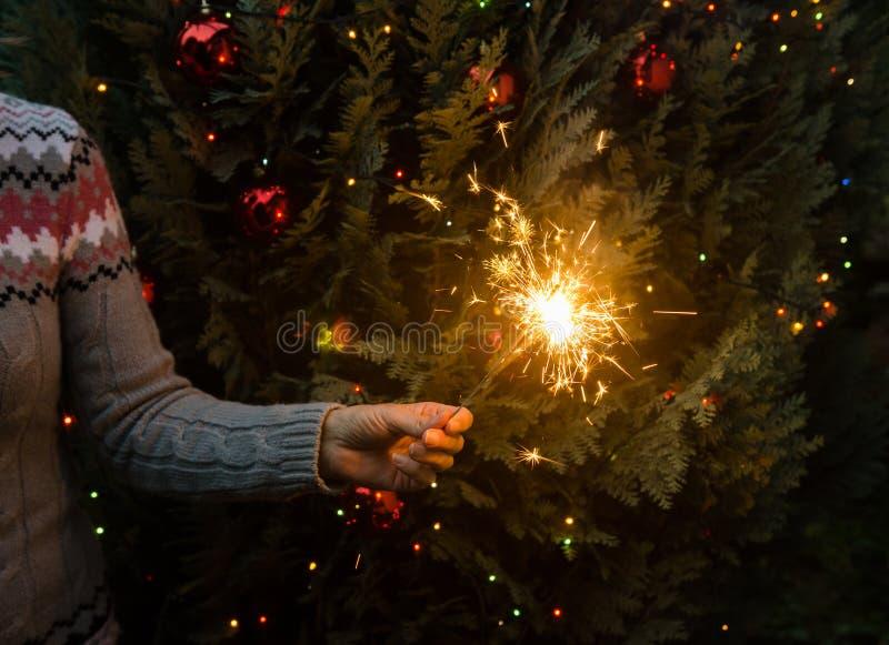 Mujer en el suéter hecho punto que sostiene bengalas antes de árbol de navidad fotos de archivo libres de regalías