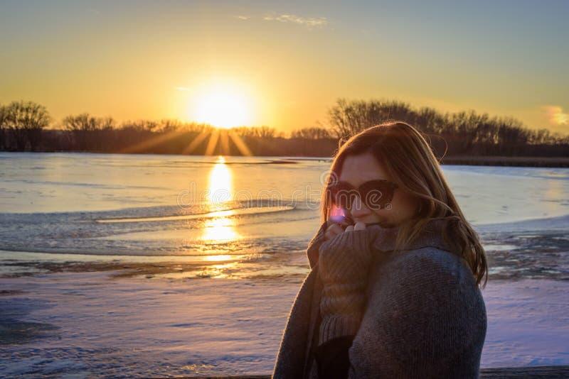Mujer en el suéter que se coloca en el puente por el lago congelado en la puesta del sol foto de archivo