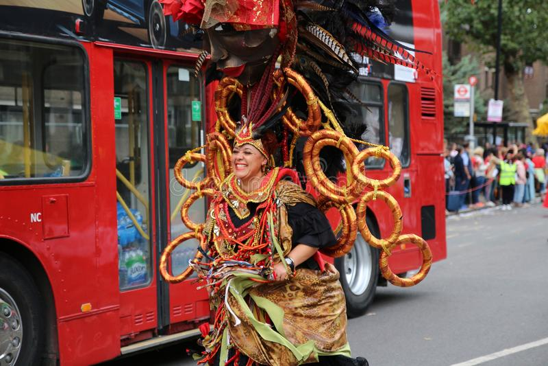 Mujer en el traje del carnaval que persigue un autobús, carnaval de Notting Hill imagenes de archivo