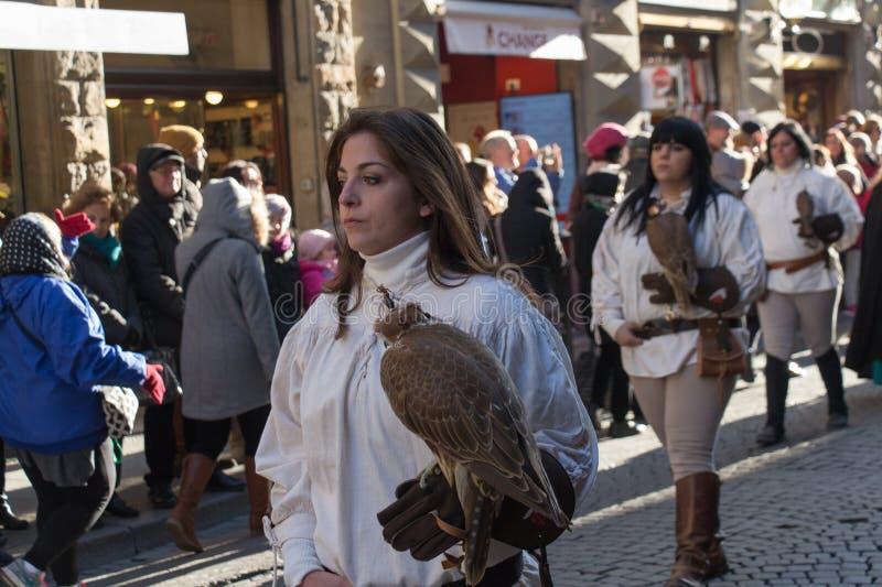 Mujer en el traje medieval que sostiene un halcón en el desfile tradicional del festival medieval de Befana de la epifanía en Flo imágenes de archivo libres de regalías