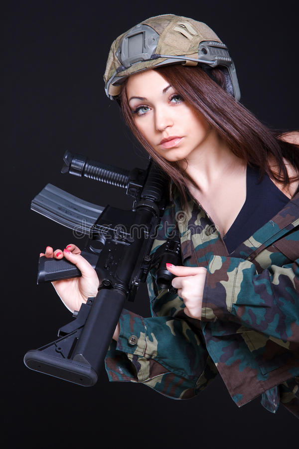 Mujer en el uniforme militar con un rifle de asalto en el shoul fotografía de archivo