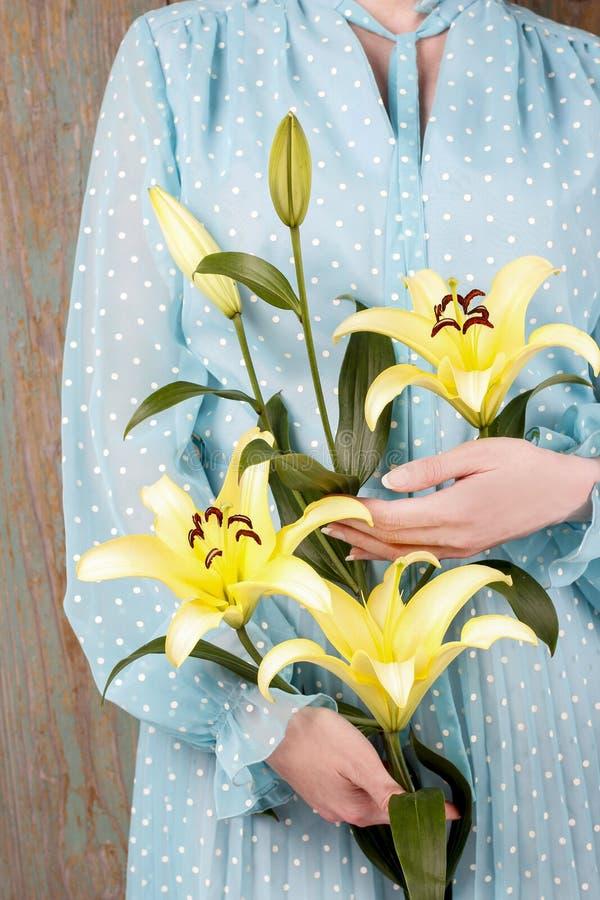 Mujer en el vestido azul del vintage que sostiene la flor amarilla del lirio fotos de archivo libres de regalías