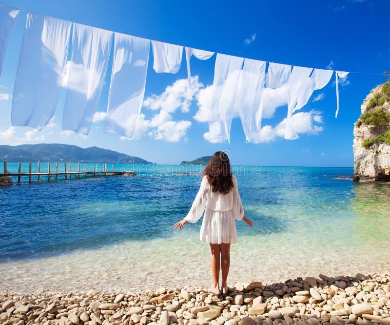 Mujer en el vestido blanco que se coloca en la playa fotografía de archivo libre de regalías