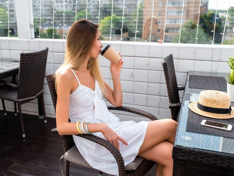 Mujer en el vestido blanco, té de consumición del café, almuerzo del desayuno, restaurante del bocado, café del verano, sentándos foto de archivo