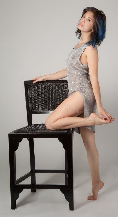 Mujer en el vestido brillante que se inclina en silla imágenes de archivo libres de regalías