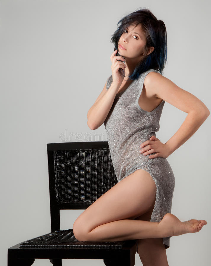 Mujer en el vestido brillante que se inclina en silla imagenes de archivo