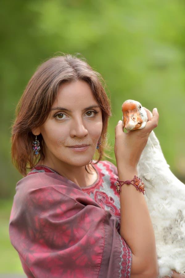 Mujer en el vestido de Borgo?a en una granja con un ganso fotos de archivo