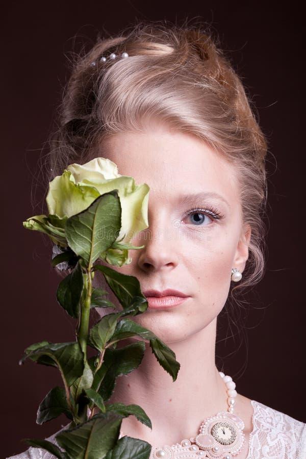 Mujer en el vestido del victorian que cubre su ojo con una rosa fotos de archivo