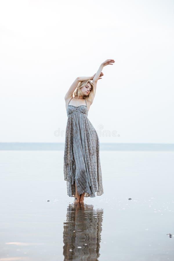 Mujer en el vestido largo que se coloca en el lago fotos de archivo libres de regalías