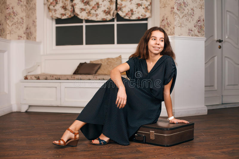 Mujer en el vestido negro que se sienta en su maleta foto de archivo libre de regalías