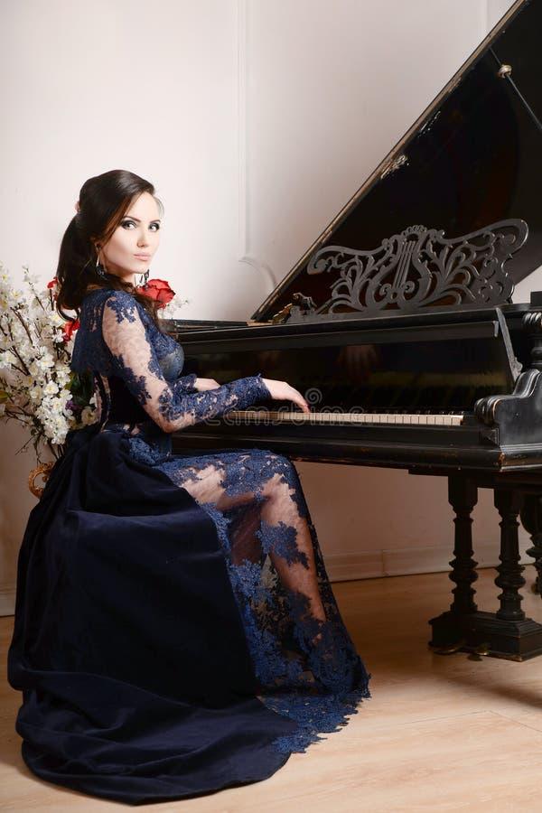 Mujer en el vestido profundamente azul del cordón que juega el piano y las flores Ilustración retra de la vendimia style fotos de archivo