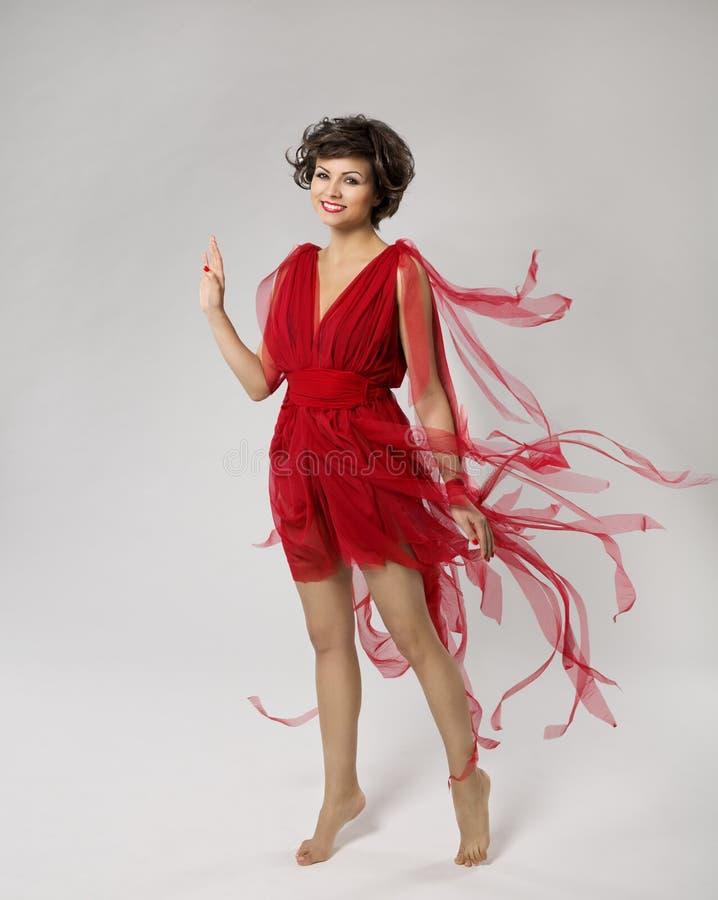 Mujer en el vestido rojo de la belleza, mano que agita de la muchacha hermosa, ropa que vuela y que agita en el viento, modelo de imagen de archivo