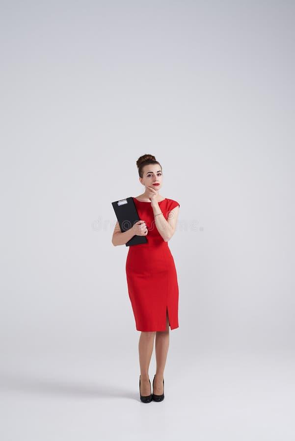 Mujer en el vestido rojo que lleva a cabo la mano en la barbilla y que parece pensativo fotos de archivo libres de regalías