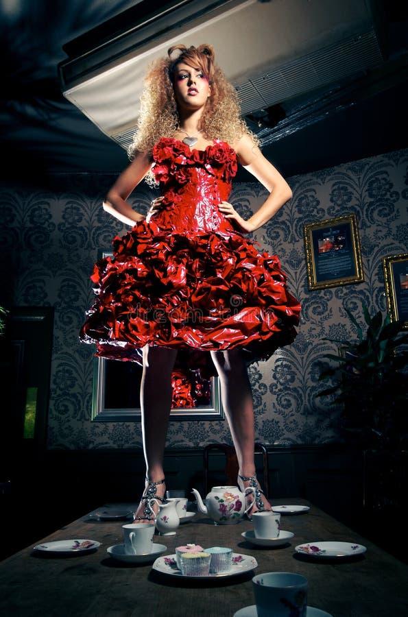 Mujer en el vestido rojo que se coloca sobre la mesa de comedor fotos de archivo