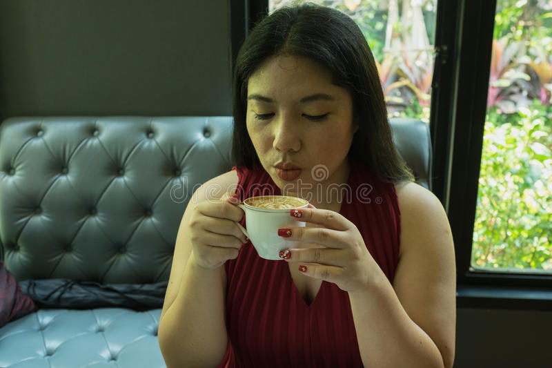 Mujer en el vestido rojo que sostiene la taza de café caliente fotografía de archivo