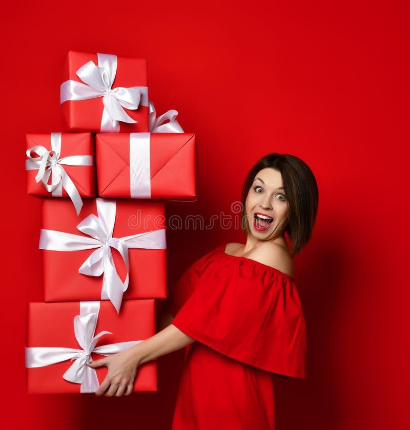 Mujer en el vestido rojo que sostiene muchas cajas imagenes de archivo