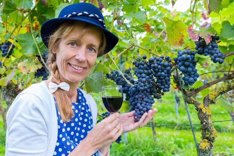 Mujer en el viñedo que muestra las uvas y el vino fotografía de archivo