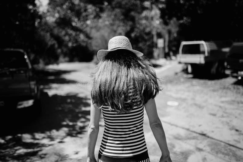 Mujer en ella detrás con el sombrero que se niega a afrontar la cámara en el campo fotos de archivo libres de regalías
