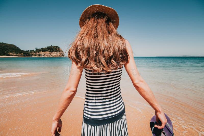 Mujer en ella detrás que entra en una playa australiana hermosa fotografía de archivo libre de regalías