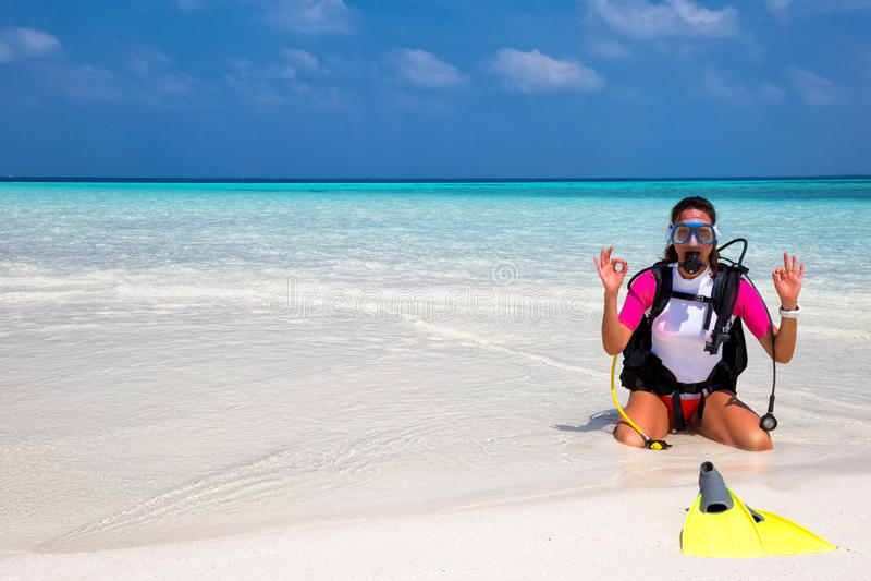 Mujer en engranaje del buceo con escafandra en una playa fotografía de archivo
