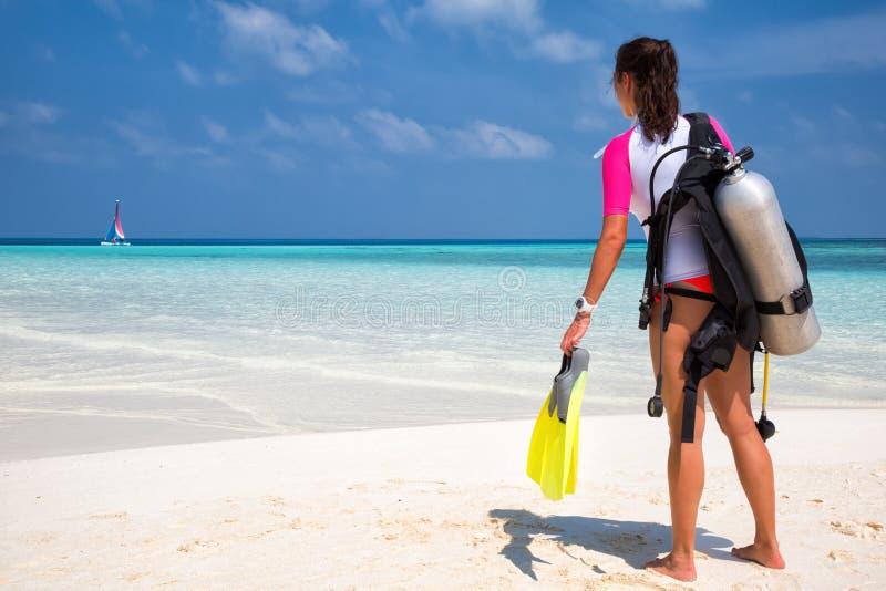 Mujer en engranaje del buceo con escafandra en una playa foto de archivo