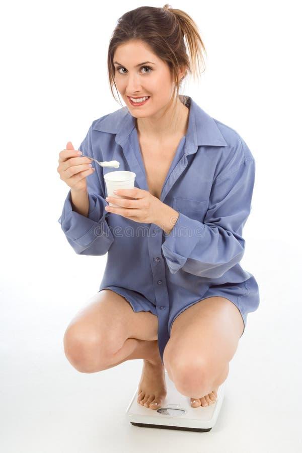Mujer en escalas del peso que come el yogur sano fotos de archivo libres de regalías