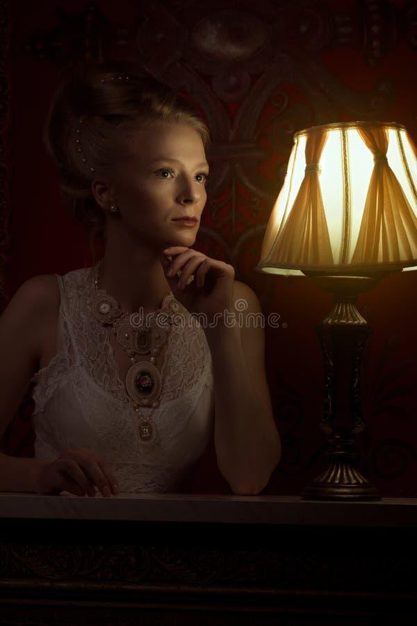 Mujer en estilo del victorian y sitio del vintage con la lámpara al lado de ella imagen de archivo libre de regalías