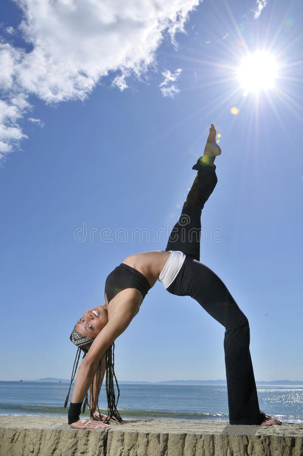 Mujer en estiramiento de la yoga en la playa fotografía de archivo libre de regalías