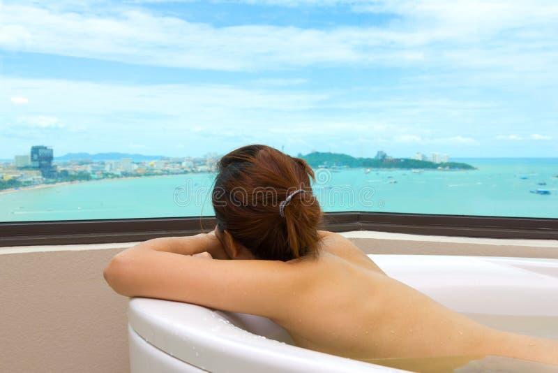 Mujer en fondo relajante de la opinión del mar de la bañera fotos de archivo libres de regalías