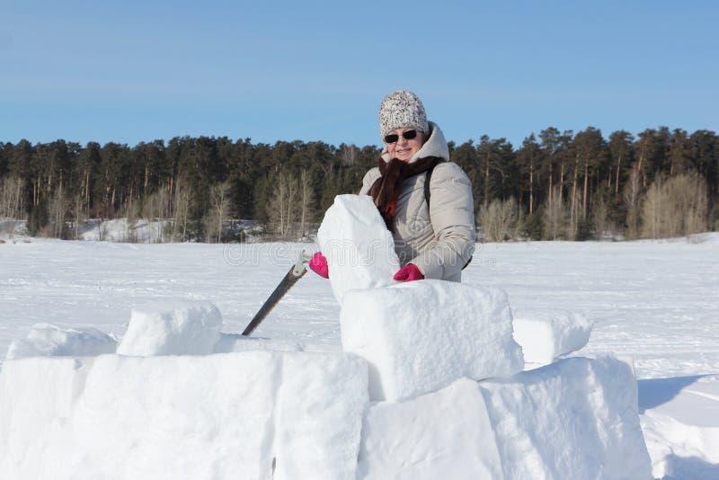 Mujer en gafas de sol con una sierra en una mano que construye un iglú, Novosibirsk, Rusia foto de archivo