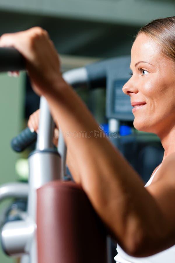 Mujer en gimnasia en el ejercicio de la máquina foto de archivo libre de regalías