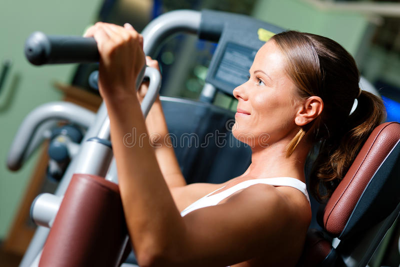 Mujer en gimnasia en el ejercicio de la máquina fotografía de archivo libre de regalías