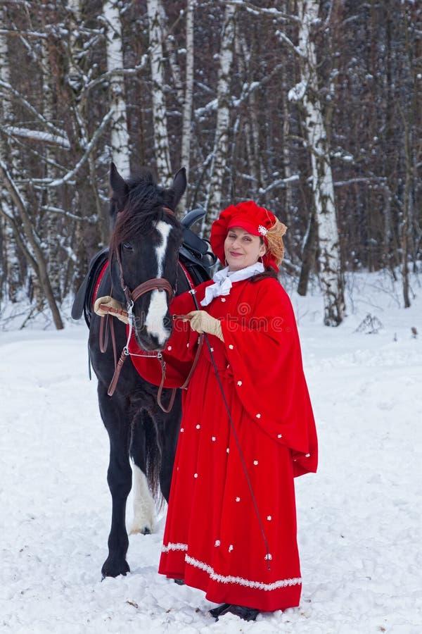 Mujer en hábito de montar a caballo rojo imagen de archivo
