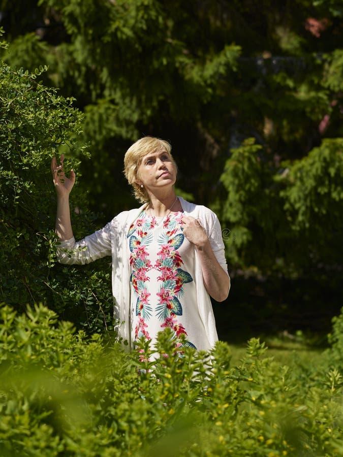 Mujer en jardín imagenes de archivo