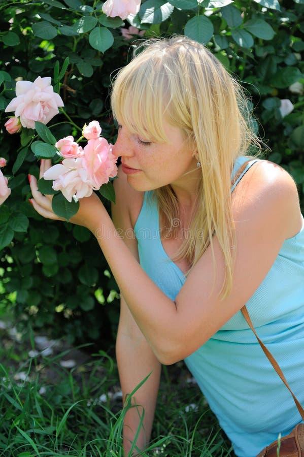 Mujer en jardín con las rosas imagen de archivo