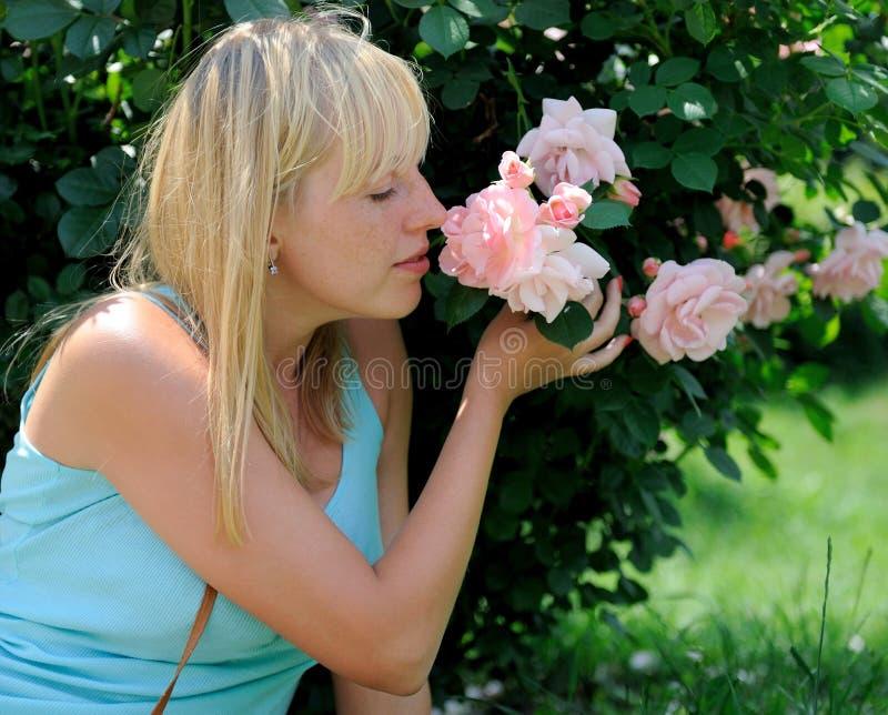 Mujer en jardín con las rosas imagenes de archivo