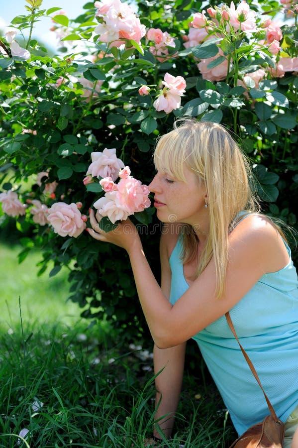 Mujer en jardín con las rosas foto de archivo