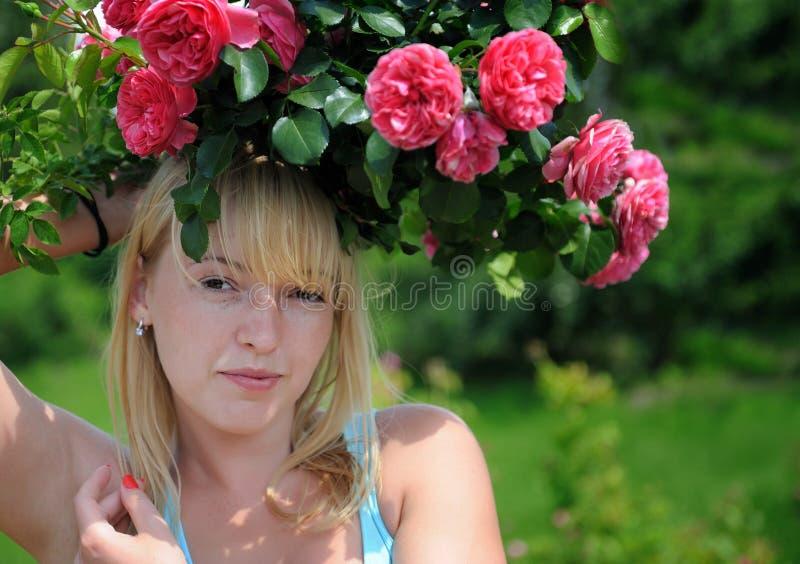 Mujer en jardín con las rosas foto de archivo libre de regalías